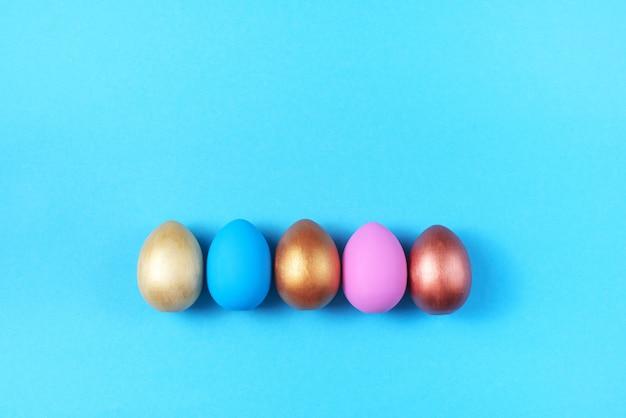 明るい青色の背景に着色された卵のイースターセットイースターの休日の装飾
