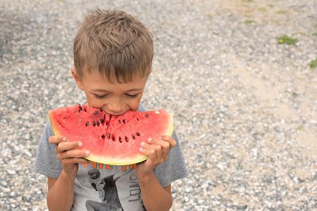 Счастливый мальчик ест спелый арбуз.