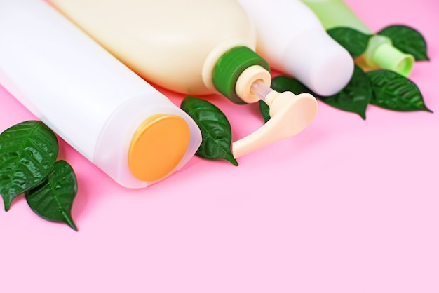 ピンクの背景に髪と体のケアのための化粧品白ボトル