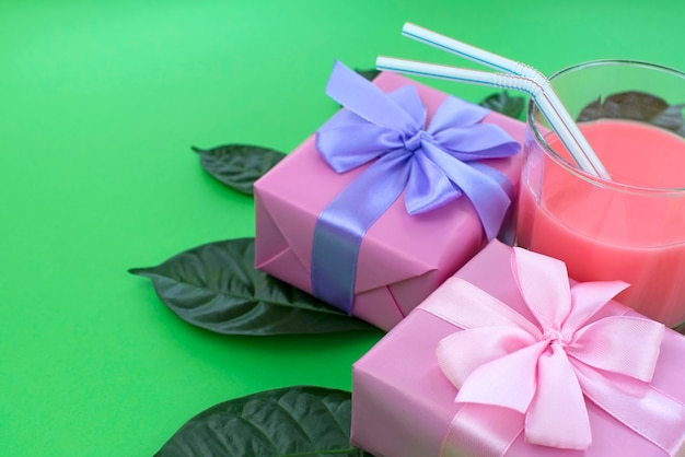 Праздничный плакат коробки с подарками стакан молочного коктейля на ярко-зеленом фоне.