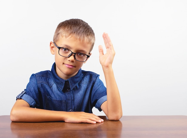 Баннер школьник в синей рубашке, сидя за столом. мальчик в очках, концепция обратно в школу