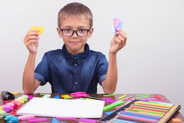 テーブルに座っている青いシャツを着て男子生徒。眼鏡をかけた少年。学校に戻るコンセプト