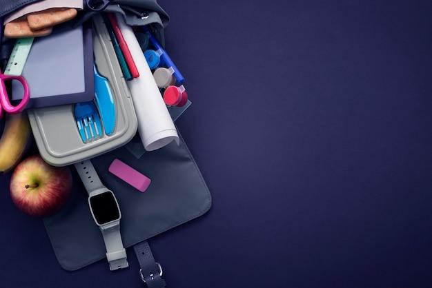 コピースペースで学校に戻るバナーの背景。黒の背景に文房具鉛筆ペン定規バックパックランチボックス