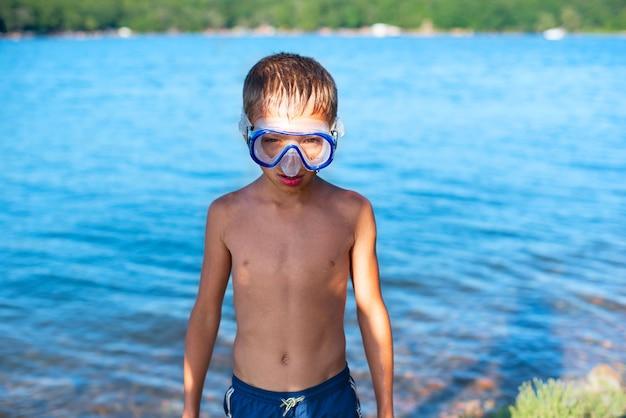 海の観光旅行のビーチでダイビングマスクの少年