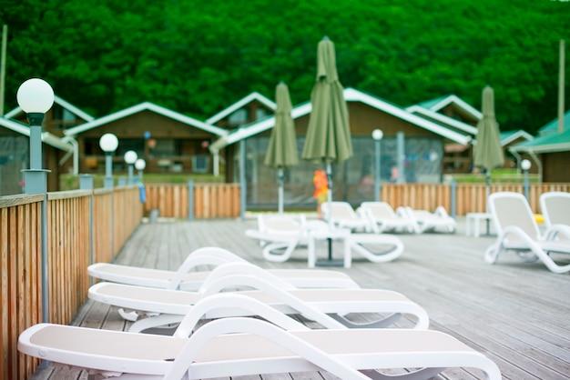 カントリークラブレクリエーションレクリエーションは、木造住宅の森の木のサンラウンジャーの傘をリラックスします。