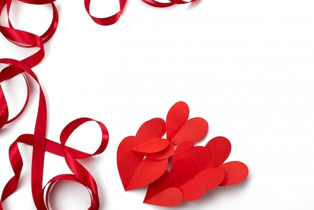 バレンタインデーのサテンの赤いリボンハートホワイトバックグラウンド概念のフレーム