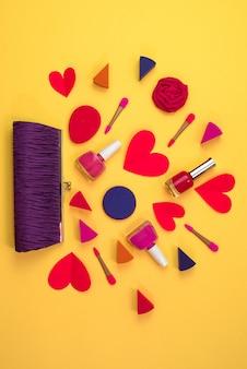 Макияж из женских аксессуаров представляет собой кошелек красное сердце на желтом фоне