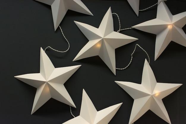 暗い背景にホワイトペーパーの星。電気クリスマスガーランド。スウェーデンのデザイン