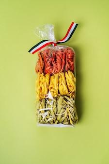 Красочные сырые итальянские макароны в прозрачный пластиковый пакет на зеленом фоне. домашняя цветная паста.