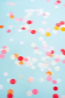 飛んで動く明るい紙吹雪。お祝いパーティーの背景。