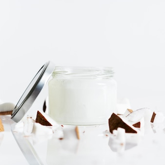 Органическое здоровое кокосовое масло в стеклянной банке с кусочками свежего кокоса на белом цвете.