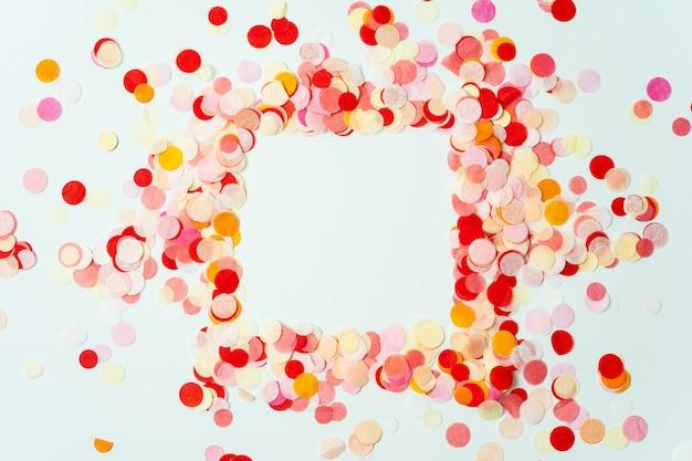パステルカラーの背景に赤とオレンジ色のお祝い紙吹雪で作られたカラフルなフレーム