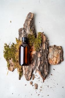 天然の樹皮の樹木、小さなコケ、ガラスの茶色のボトルに入ったオーガニック化粧品の草。平干し、