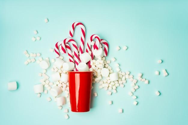 赤いマグカップとさまざまなサイズのマシュマロが散らばったキャンディー杖
