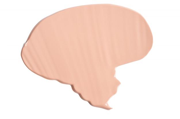 Аккуратно бежевый мазок макияж крем основа на белом фоне. текстура жидкой основы.