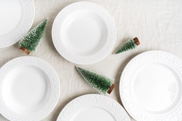 コピースペース付きのリネンテーブルクロスに白い皿、カトラリー、ナプキン、クリスマスの装飾とクリスマステーブルの設定の準備。冬、新年のお祝いコンセプトテーブル。