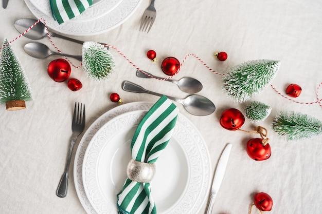 白いプレート、カトラリー、ナプキン、コピースペース付きのリネンテーブルクロスにクリスマスの装飾とクリスマステーブルの設定。冬、新年のお祝いコンセプトテーブル。