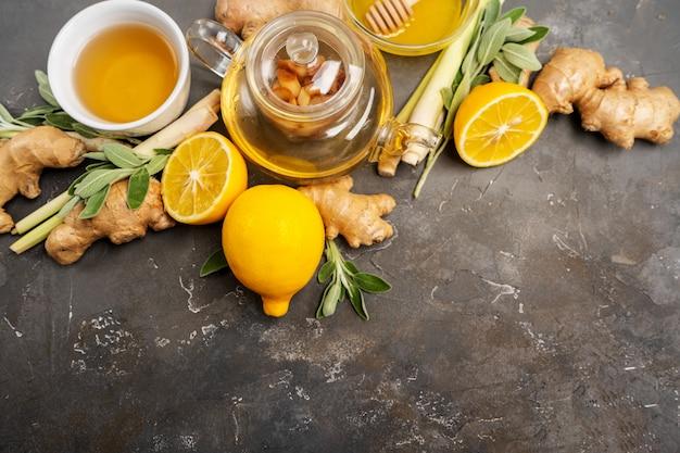 Делая здоровый антиоксидант и противовоспалительный имбирный чай со свежим имбирем, лимонник, шалфей, мед и лимон на темном фоне с копией пространства.
