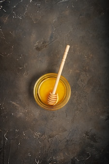 蜂蜜とコピースペースで暗い背景に蜂蜜スプーン。上から撮影。
