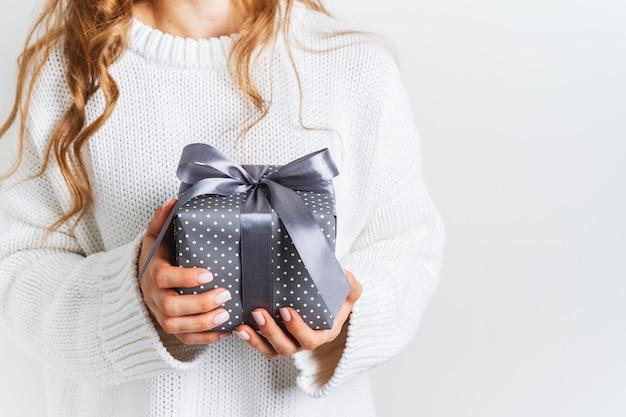 弓でギフトボックスを保持しているウールの白いセーターの女性。クリスマスのお祝いレイアウト。新年のモックアップ。