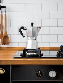白いタイルと壁にガスストーブのモカコーヒーポットのクローズアップ。