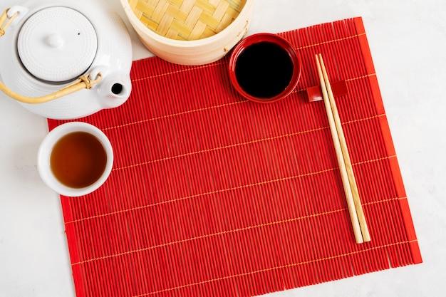 アジアのお茶の食べ物の背景。灰色の石の背景に赤い竹マットに箸でティーポットとカップ。メニューのモックアップ。