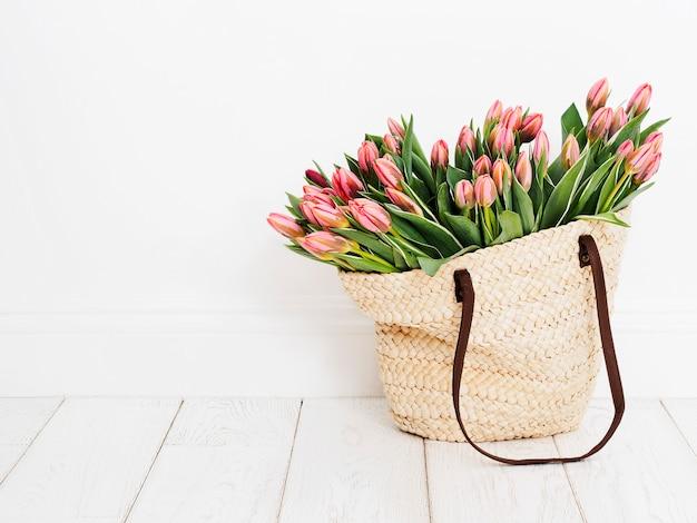 白い壁の前にチューリップを織り込んだエコフレンドリーなショッピングバッグ