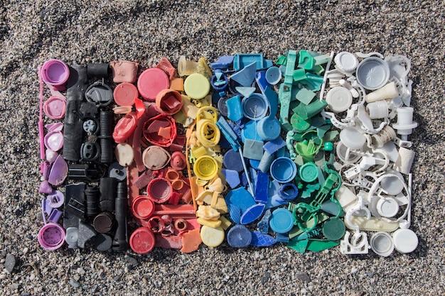 プラスチックパーツのグラデーションの色、ビーチで見つかったプラスチックキャップとさまざまなプラスチック片の劣化した静物、ビーチで見つかったプラスチック片の静物写真の航空写真