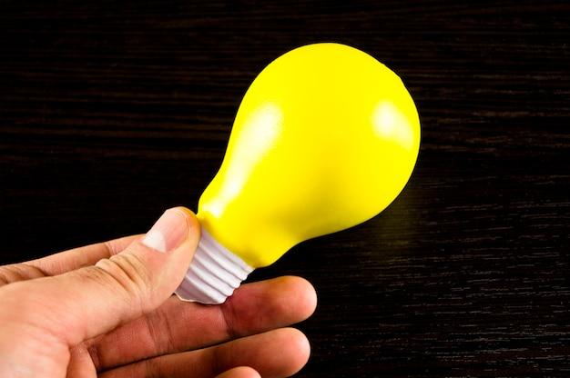 暗い背景上のアイデアのシンボルとして黄色の電球