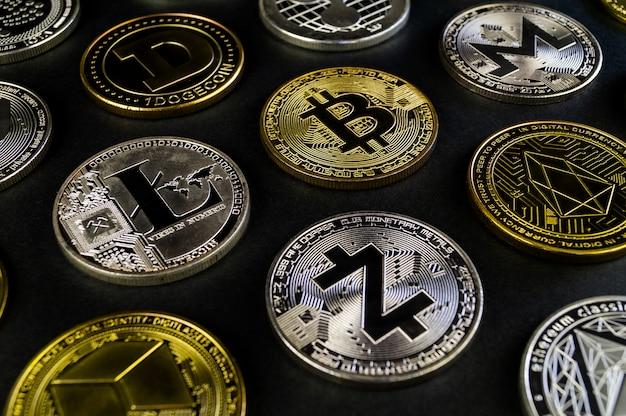 Много криптовалютных монет лежат на темной поверхности