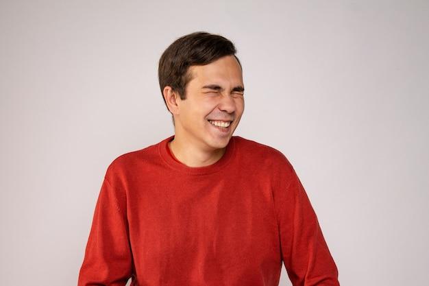 赤いセーターを着た若い男が笑います。肖像画