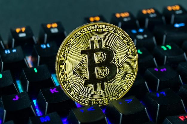 Монета криптовалюта биткойн крупным планом клавиатуры с цветовой кодировкой.