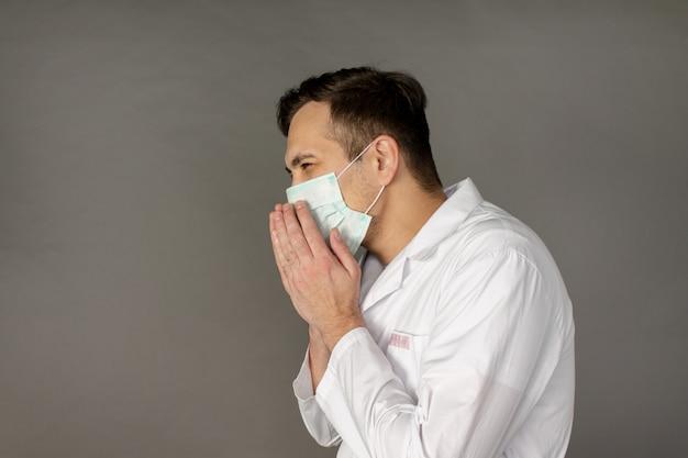 医師は咳をし、コロナウイルスから保護するためにマスクを着用します