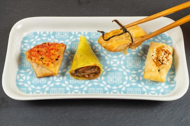 アジア料理の選択。アヒルのコーン、小包、生姜と醤油のバスケット、ティッカクラッカー、風車