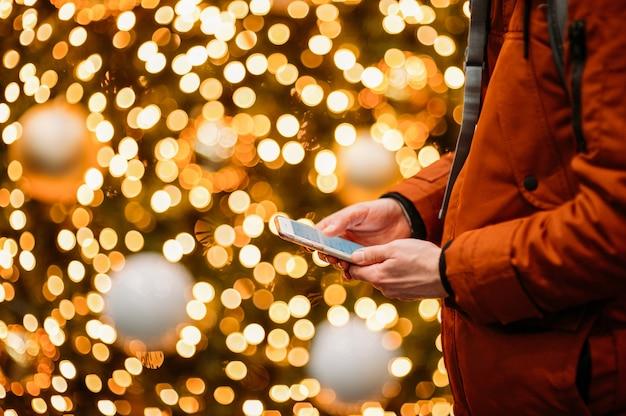 照らされたクリスマスツリーに対してスマートフォンを使用している人