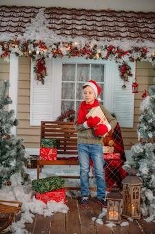 クリスマスの装飾のプレゼントと幸せな少年