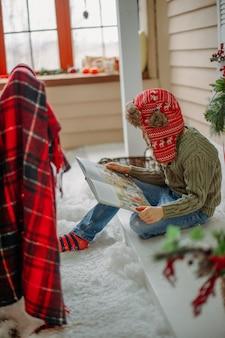 Мальчик читает книгу на рождество