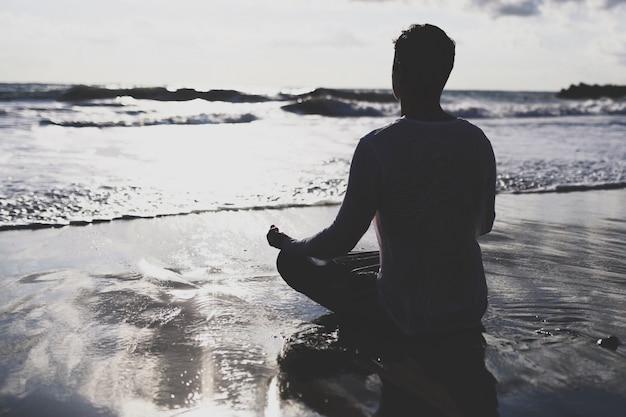 Йога практики молодого человека на пляже на заходе солнца.