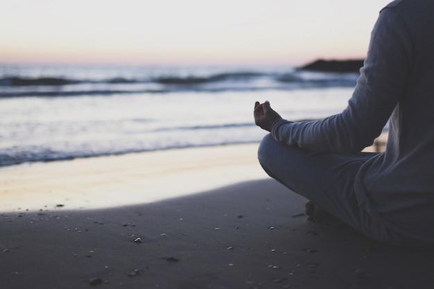若い男は夕暮れ時のビーチでヨガを練習します。