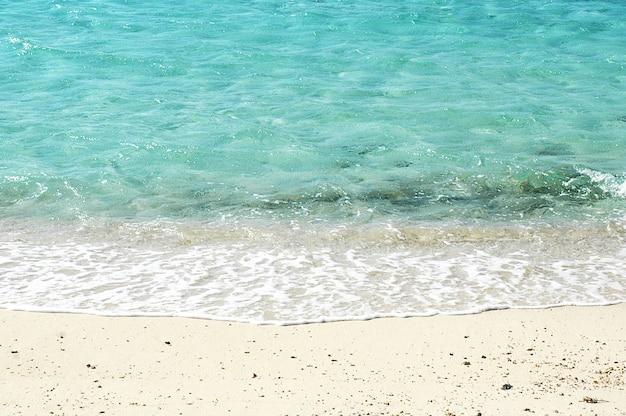 砂浜で青い海の柔らかい波。