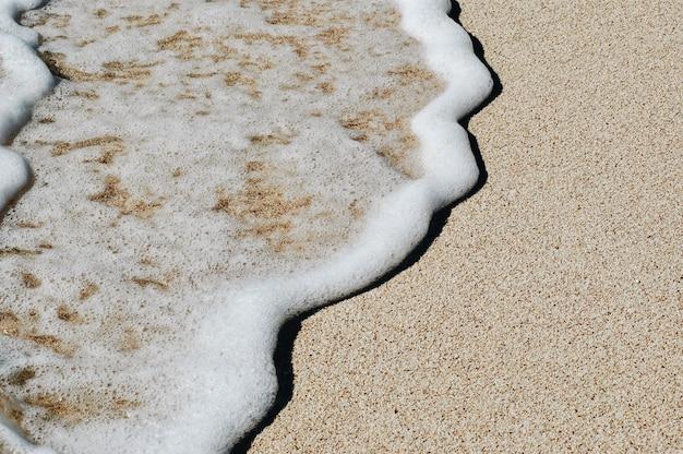砂浜で青い海の柔らかい波。バックグラウンド。