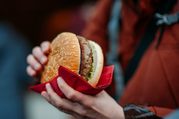 Человек ест большой гамбургер