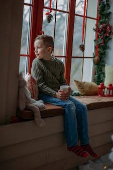 Счастливый мальчик с горячим напитком в рождество