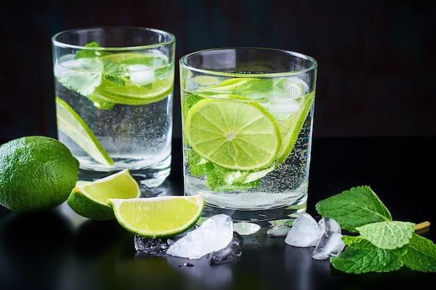 夏の飲み物レモネードモヒート、ライム、ミント、氷と黒の背景
