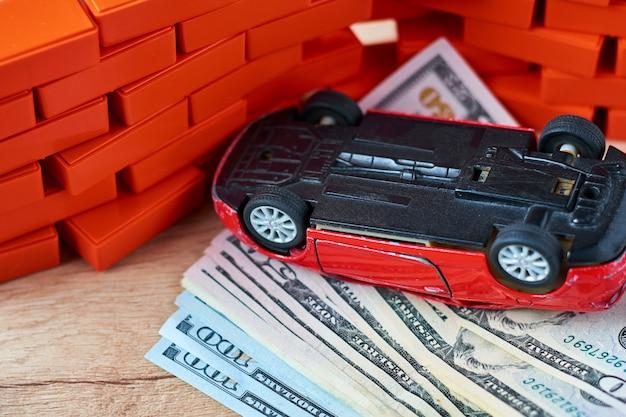 ドル札の山の上に倒された車。自動車保険のコンセプト、事故後の損害