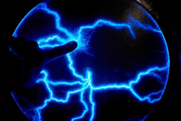 Палец сенсорный электрический плазменный шар на темном фоне. модель статического электричества