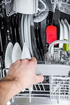 男は食器洗い機からきれいな皿をアンロードします