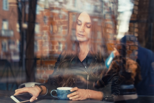 魅力的な若い女性がカフェで携帯電話を使用して