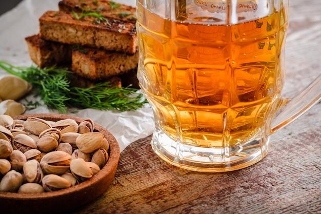 軽めのビールと木製のテーブルの上の軽食のマグカップ
