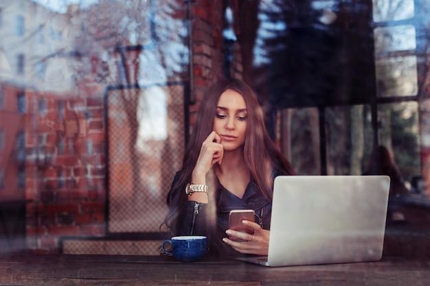 コンピューターで働くカフェの窓の外の若い女の子